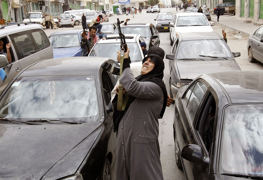 A woman rebel fighter supporter shoots an AK-47 rifle as she reacts to the news of the withdrawal of Libyan leader Muammar Gaddafi's forces from Benghazi March 19, 2011