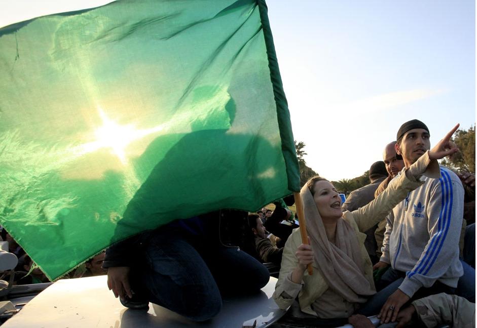 Aisha Gaddafi, daughter of Libya's leader Muammar Gaddafi, greets supporters at Bab Al-Aziziyah in Tripoli March 19, 2011.