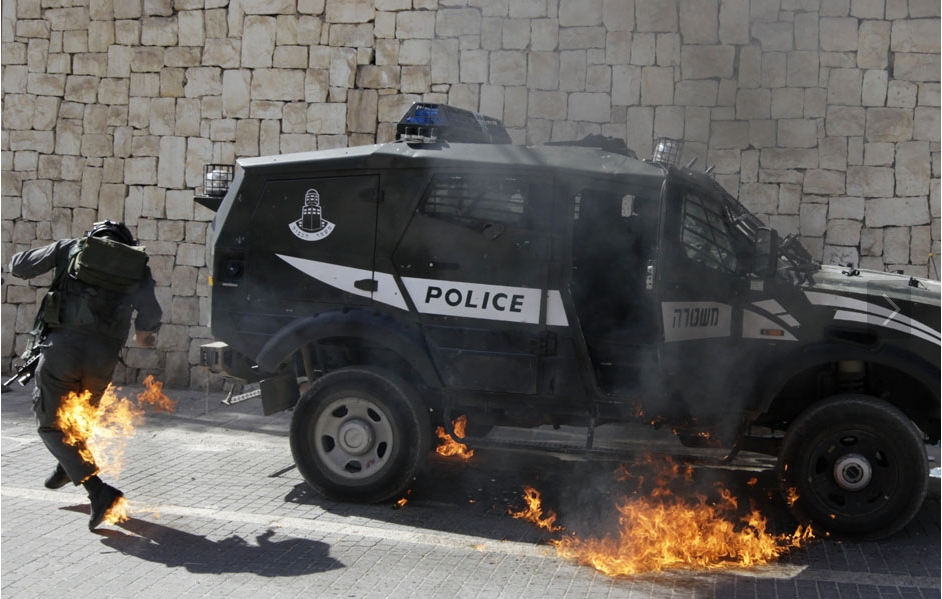 An Israeli border police officer tries to escape from flames after a petrol bomb was thrown at him during clashes with Palestinians  Silwan in East Jerusalem March 18 11