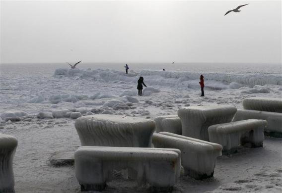 People walk along a snowy beach on the bank of the frozen Black Sea in the Ukrainian port of Odessa February 6, 2012.