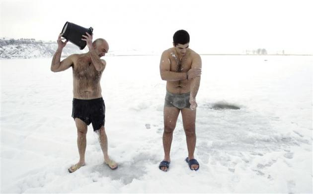 A man pours water on himself as another rubs himself with snow on the ice-covered Lisi Lake