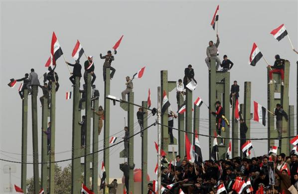 Supporters of anti-U.S. Shi'ite cleric Moqtada al-Sadr wave Iraqi flags during a rally in Baghdad, February 9, 2012.