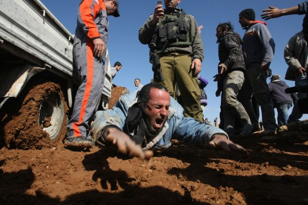 An injured Palestinian worker screams in pain after an Israeli army driver drove a trailer over his legs, as he tried to block him from building a house in West Bank on January 25, 2012.