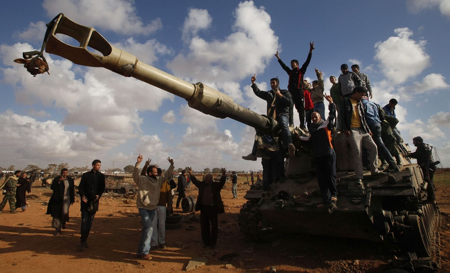 People celebrate atop a destroyed tank belonging to forces loyal to  Gaddafi after an air strike by coalition forces along a rd betn Benghazi and Ajdabiyah March 20 2011