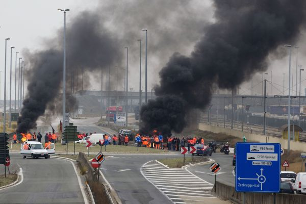 Members of different unions block the entrance road to the harbor of Zeebrugge, part of a nationwide general strike in Belgium on January 30, 2012.