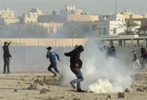 A mourner kicks a tear gas canister fired by riot police after the funeral of Mowali in Muharraq