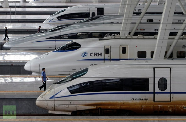 Train employee walks past a CRH Harmony 380BL bullet train at Beijing South Railway Station