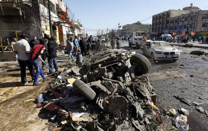 Residents gather at the site of a car bomb attack in the AL-Mashtal district in Baghdad