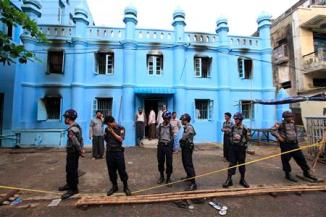 Police stand in front of a mosque and school dormitory that were damaged by a fire in Yangon