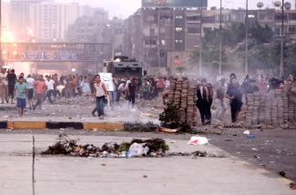 Opponents of deposed Egyptian President Mohamed Mursi throw stones at his supporters during clashes in Nasr city area