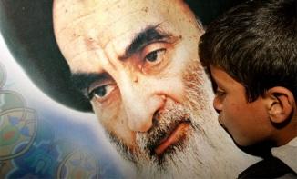 IRAQI SHI'ITE BOY KISSES POSTER OF AYATOLLAH ALI AL-SISTANI IN KARBALA.