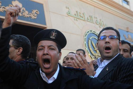 Police officers take part in a sanctioned protest outside the Interior Ministry building in Cairo