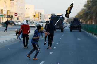 Anti-government protesters throw stones at riot police after the funeral procession for Asma Hussain, in the village of Jid Al Haj