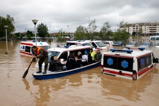 Serbian rows a boat past flooded ambulance vehicles in the flooded town of Obrenovac