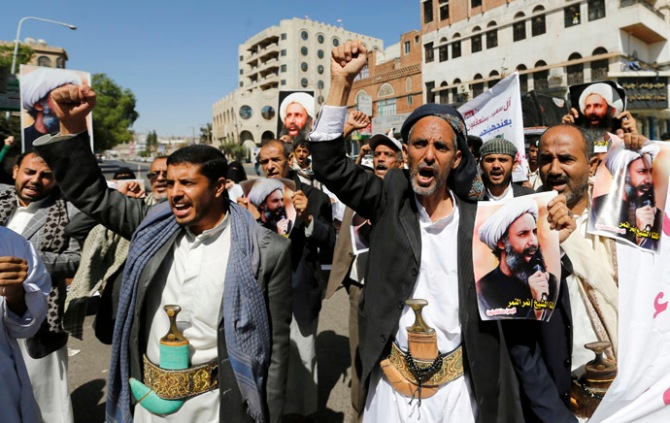 Shi'ite protesters shout slogans as they hold posters of Sheikh Nimr al-Nimr during a demonstration outside the Saudi embassy in Sanaa