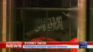 Video grab shows a black flag with white Arabic writing held up at the window of the Lindt cafe, where hostages are being held