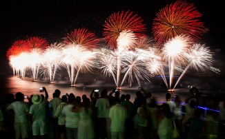 People watch fireworks exploding over Copacabana beach during New Year celebrations at the Pavao Pavaozinho slum in Rio de Janeiro
