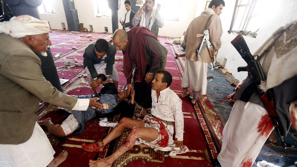 People react after being injured in bomb attack inside a mosque in Sanaa