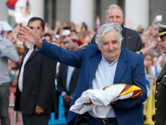Uruguay's President Jose Mujica waves to the people after receiving the Uruguayan flag on the last working day of his term in Montevideo