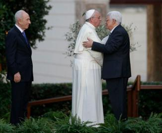 FILE - In this Sunday, June 8, 2014 file photo Pope Francis and Palestinian President Mahmoud Abbas embrace each other as Israel's President Shimon Peres, left, looks at them during an evening of peace prayers in the Vatican gardens. The Vatican officially recognized the state of Palestine in a new treaty finalized Wednesday, May 13, 2015 immediately sparking Israeli ire and accusations that the move hurt peace prospects. The treaty, which concerns the activities of the Catholic Church in Palestinian territory, makes clear that the Holy See has switched its diplomatic recognition from the Palestine Liberation Organization to the state of Palestine. (AP Photo/Gregorio Borgia, File)