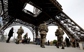 French soldiers patrol the area at the foot of the Eiffel Tower