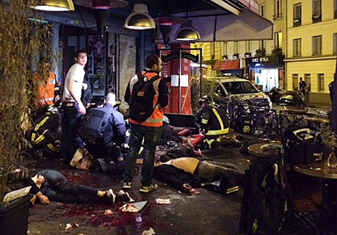 Victims of a shooting attack lay on the pavement outside La Belle Equipe restaurant in Paris Friday, Nov. 13, 2015. Well over 100 people were killed in Paris on Friday night in a series of shooting, explosions. (Anne Sophie Chaisemartin via AP) MANDATORY CREDIT